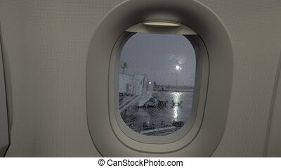 A closeup of a porthole and a rainy airport courtyard behind...