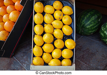 A closeup of bright lemons in a box