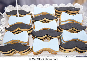 A closeup of cookies with mustache and bowtie decorations on a tray under the lights