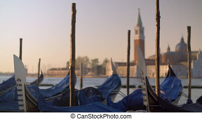 A closeup of covered gondolas swaying on a pier against the blurred Venice view