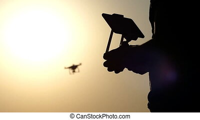 A closeup of male hands, control panel, and a flying drone at sunset