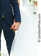 A closeup of newlyweds hands holding each other tightly