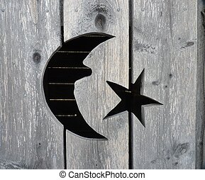 A closeup of the moon and star cutout on a rustic wooden...