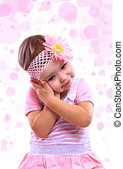 A closeup portrait of a happy little girl against the white background with bokeh
