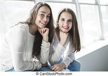 closeup portrait of hugging 2 beautiful young women having fun