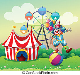 A clown balancing above an inflatable ball at the carnival -...