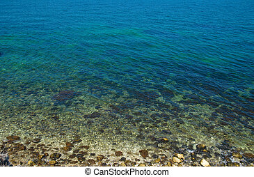 A coast with stones and blue ocean water.
