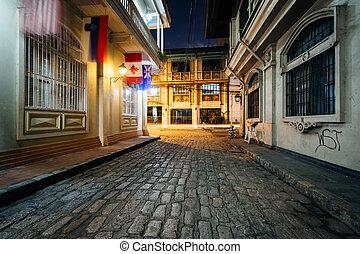 A cobblestone street at night, in Intramuros, Manila, The Philippines.