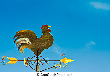 a cockerel wind vane against blue sky