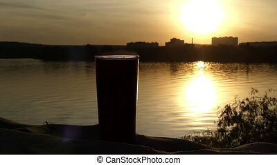 A coffee cup stands on a sandy beach of a lake at a nice sunset in slow motion