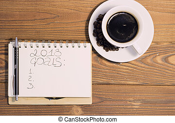 A coffee cup with a notebook on a wooden background