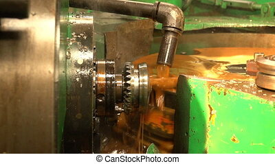 A cogwheel turning slowly ith a metal workpiece and pouring...