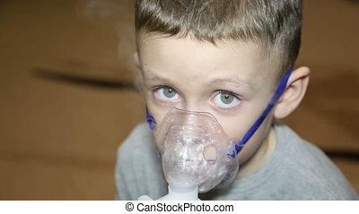 A cold boy breathes in an inhaler - White boy is having...