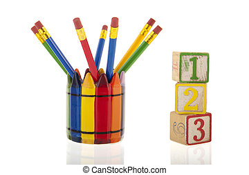 A collage of colourfull pencils in a cup next to three 1-2-3 cubes isolated over a white background