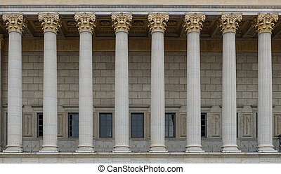 A colonnade of a public law court. A neoclassical building with a row of corinthian columns.