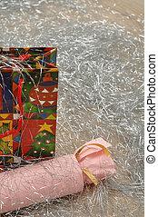 A colorful christmas gift bag with a christmas cracker displayed on tinsel