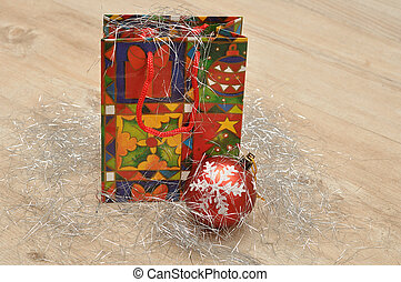 A colorful christmas gift bag with a christmas tree bauble displayed on tinsel