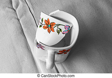 A colorful cup broken and placed on a white cloth.