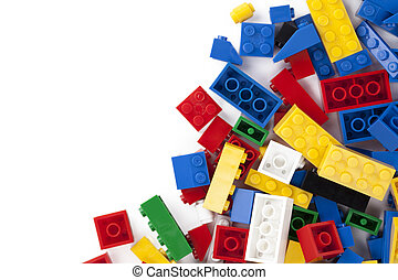 Close-up image of colorful lego bricks scattered on the side of a white background