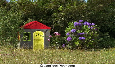 Wide shot of a colorful, large play house near a bush with enormous purple flowers