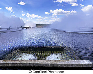 A colorful sight: cooling fountains of the Atomic Station, Heat of a power plant against a background of white clouds, blue sky.