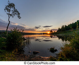 colorful sunset over a calm lake with reflections in the water and rocks and reeds in the foreground