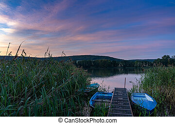 colorful sunset over lake landscape with small rowboats
