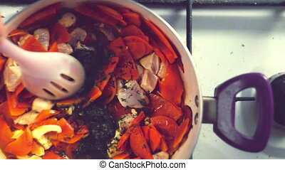 A colorful variety of vegetables, boiling in a pan on the stove. Top view.