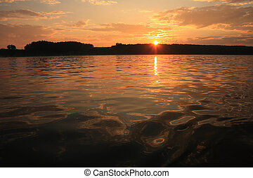 Sunset above the shore horizon viewed from a boat on the water