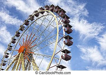 A colourful ferris wheel against a deep blue sky