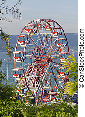 A colourful ferris wheel in the city amusement park at sunny summer day over blue sky background. Front view through green trees. Entertainment concept