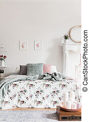 A comfortable bed with a rose pattern coverlet and fluffy pillows in a feminine bedroom interior. Real photo.
