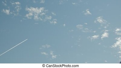 A commercial airliner is flying diagonally left to right of...