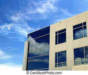 A commercial building with reflective mirror windows and beautiful blue sky background