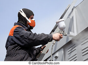 A commercial painter on the stairs spray painting a steel exterior wall against the blue sky