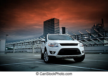 A compact SUV in the city. Dramatic sky.