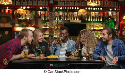 A company of young men and women sitting in a bar at a table...