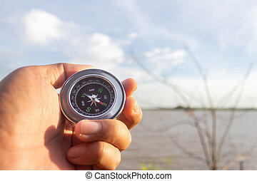 A compass in the palm of my hand that is looking for a destination on the river