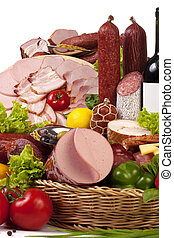 A composition of meat and vegetables with a bottle of wine isolated on white