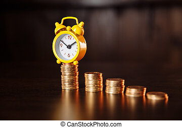 A concept about the relationship between time and money. An alarm clock and stack of coins