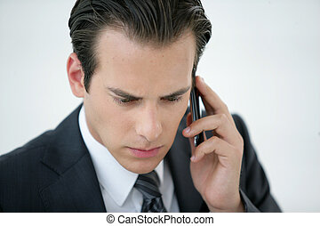 A concerned businessman talking on his mobile phone