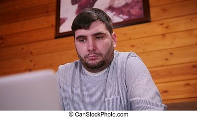 A concerned man freelance worker sitting by the laptop. Mid...