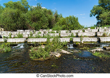 Concrete blocks lying on a small river - dam