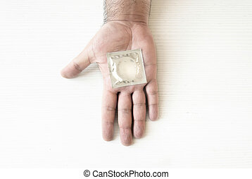 a condom packed on the palm of a male hand
