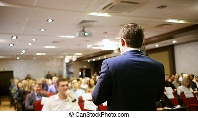 A conference in the hall. A man talking on the stage. Mid shot