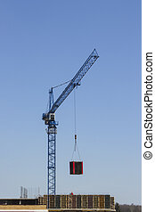 A construction crane moves the load. Building materials on pallets. Construction of a modern residential building