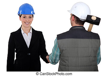 a construction manager and a worker shaking hands
