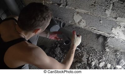 a construction site, a worker, laying sewer pipes in a new house.