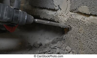 a construction site, a worker pounding the wall with a...