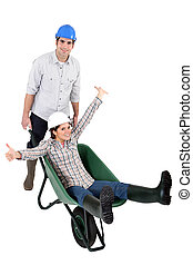 a construction worker carrying his female colleague in a wheelbarrow